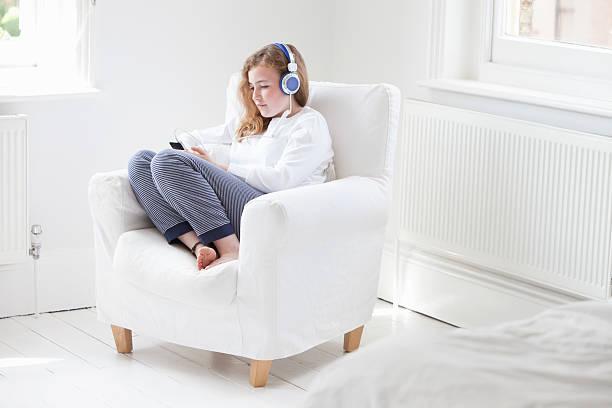Jeune fille qui profite du chauffage dans le salon en écoutant de la musique