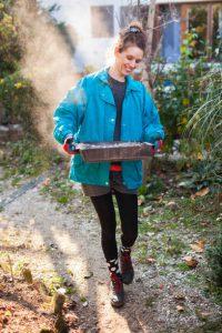 Jeune femme transportant le bac à cendres de son poêle à bois dehors
