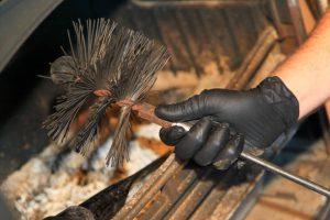 Main de ramoneur avec outil pour nettoyer conduit cheminée