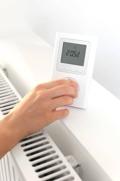 Personne réglant le thermostat d'un chauffage dans une maison bien isolée