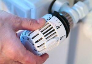 Homme en train de régler la température d'un radiateur
