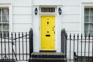 Porte d'entrée jaune vif avec escaliers et grille noirs